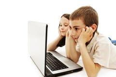 Studio die van twee jonge geitjes met laptop is ontsproten stock fotografie