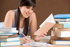 Studio domestico - l'adolescente della donna scrive le note Immagine Stock