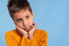 Studio emotional shot of a boy in a yellow shirt on a blue background with copy space. He touches the palms of his cheeks and stock photos