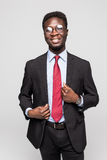 Studio fashion portrait of a handsome young African American businessman wearing a black suit and tie. Isolated on gray background Royalty Free Stock Photo
