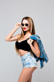 Studio fashion portrait stylish woman in sunglasses and a denim dress. Young slim girl with red lipstick holding a hand Stock Photos