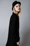 Studio fashion portrait of yong pretty woman in black coat Royalty Free Stock Images