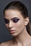 Studio fashion portrait of yong pretty woman. Make-up, purple ey. Studio fashion portrait of yong pretty woman. Gray background Stock Images