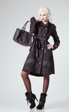 Studio fashion shot: beautiful girl in black coat and boots, with bag in hand Stock Images