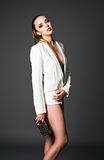 Studio fashion shot: beautiful girl in white jacket with clutch Stock Photos