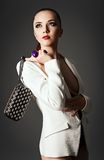 Studio fashion shot: beautiful girl in white jacket with clutch in hands Stock Image