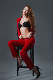 Studio fashion shot: beautiful sexy young woman in black lingerie and red costume sitting on a stool Stock Photo