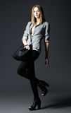 Studio fashion shot: beautiful young woman in leggings and jacket, with bag Stock Photo