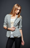 Studio fashion shot: beautiful young woman in leggings, jacket and shirt Royalty Free Stock Image