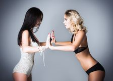 Studio fashion shot: challenge between two lovely women (blonde and brunette) in underwear Royalty Free Stock Images