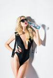 Studio fashion shot: girl in swimsuit drinking mineral water Stock Image