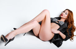 Studio fashion shot: gorgeous sexy young girl in lingerie and leather jacket lying on a floor Stock Photo