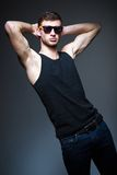 Studio fashion shot: handsome young man wearing jeans, shirt and sunglasses Stock Photography