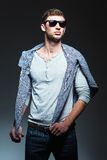 Studio fashion shot: handsome young man wearing jeans, shirt and sunglasses Stock Image
