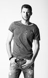 Studio fashion shot: portrait of handsome young man wearing jeans and shirt. Black and white Royalty Free Stock Image