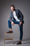 Studio fashion shot: portrait of handsome young man wearing jeans, shirt and jacket Stock Photos