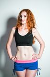 Studio fashion shot: seductive ginger woman wearing shorts and shirt Royalty Free Stock Photos