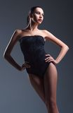 Studio fashion shot: seductive young woman wearing black swimsuit Royalty Free Stock Photos