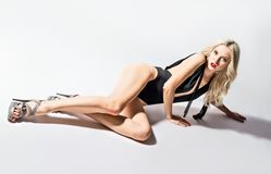 Studio fashion shot: a sexy young woman in swimsuit lying on the floor Royalty Free Stock Photo