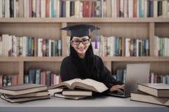 Studio felice del laureato della femmina alla biblioteca con il computer portatile Fotografie Stock