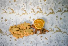 Christmas food photography gingerbread man men with spice cinnamon sticks orange fruit slice on gold reindeer wrapping paper Royalty Free Stock Photos