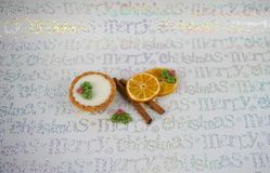 Shiny silver Christmas food photography picture with iced mince pie seasonal spice cinnamon sticks orange slice holly and berry royalty free stock photography