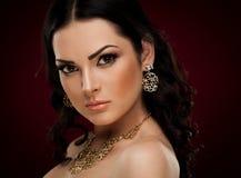 Studio, framsida, bruna ögon, halsband och örhängen, röd bakgrund Royaltyfri Fotografi