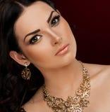 Studio, framsida, bruna ögon, halsband och örhängen, röd bakgrund Royaltyfria Bilder
