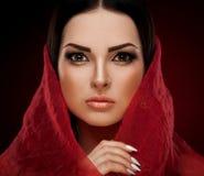 Studio framsida, bruna ögon, röd sjal, röd bakgrund Royaltyfri Foto