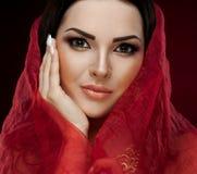 Studio framsida, bruna ögon, röd sjal, röd bakgrund Fotografering för Bildbyråer
