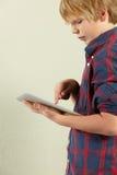 Studio geschossen vom jungen Jungen-Holding-Tablette-Computer Stockfotografie