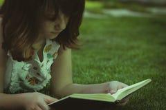 studio Giovane bella ragazza che legge un libro esterno Immagine Stock