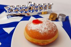 Studio Haunkkah Objects. Photo of a white and blue Israeli flag with the star of David with chocolate coins, sufganiya and silver menorah - objects for the Royalty Free Stock Photo