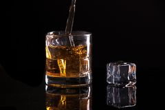 Emotive image of pouring liquor. A studio image of a glass filled with ice and liquor Royalty Free Stock Photo