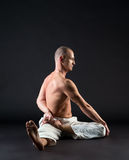 Studio image of middle-aged man doing yoga pose Stock Image