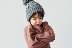 Studio image of pretty angry little girl with grumpy emotion in the winter warm gray hat, wearing sweater isolated on a white stock photos