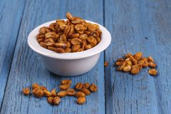 Bowl full of roasted peanuts. A studio image of roasted peanuts in a dish with some spilling over Stock Image