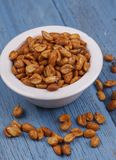 Closeup of roasted peanuts. A studio image of roasted peanuts in a dish with some spilling over royalty free stock images