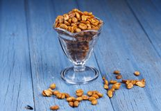 Glass dish filled with peanuts. A studio image of roasted peanuts in a dish with some spilling over Royalty Free Stock Photo
