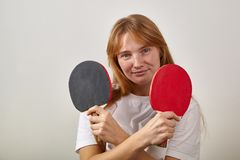 Portrait of young girl with red hair and freckles dressed in white t-shirt holding table tennis racket stock photo