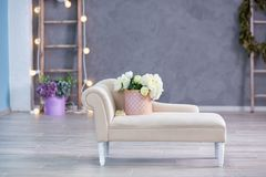 Studio interier decoration with flowers in light warm colors and casual vintage furniture stock images