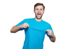 Studio isolated portrait of excited young man. Casual smiling excited man pointing with both hands to his blank blue t-shirt isolated on white background royalty free stock image