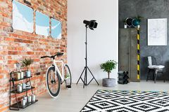 Studio lamp in the corner. Black studio lamp standing in the corner of room with brick wall and bicycle Royalty Free Stock Photography