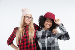 Studio lifestyle portrait of two best friends hipster girls going crazy and having great time together. Isolated on Stock Photography