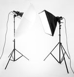Studio lighting. Two professional studio lights, with soft box and umbrella on tripods on white background Stock Image