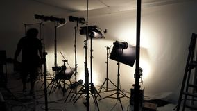 Studio lighting setup for photo shooting production. Studio lighting setup for photo shooting production with many equipment such as softbox, backdrop paper stock image