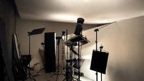 Studio lighting setup for photo shooting production. Studio lighting setup for photo shooting production with many equipment such as softbox, backdrop paper Stock Images