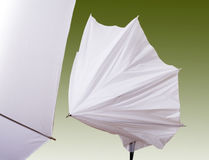 Studio lighting umbrellas. 'White studio umbrellas on green royalty free stock image
