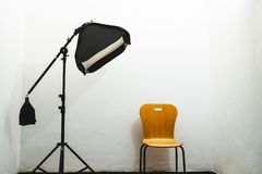 Studio lighting. View of light stand softbox and chair isolated photographer professional setup shot creative white lamp equipment flash studio background stock photography