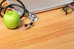 Studio macro of a stethoscope apple pen eyeglass and notebook wi Stock Photos
